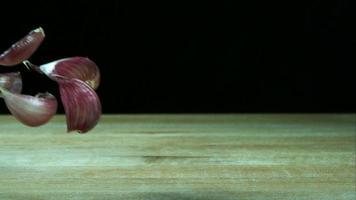 Knoblauchzehenstücke springen in Ultra-Zeitlupe (1.500 fps) auf einer Holzoberfläche - Grillphantom 029