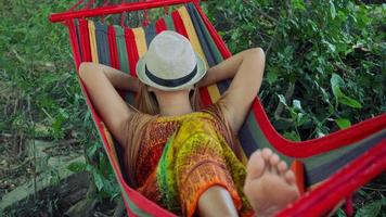 Young woman sleeping in hammock with hat covering face