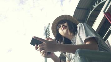 hermosa joven asiática escuchando música en un teléfono inteligente en la ciudad. joven asiática relajante escuchando música en la calle.