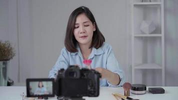 Feliz sonriente mujer asiática o blogger de belleza con pincel y cámara grabando video y agitando la mano en casa. concepto de gente de blogs de videoblog de belleza.