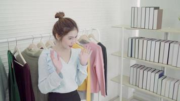 Asian fashion female blogger online influencer holding shopping bags and lots of clothes on clothes rack for recording new fashion video broadcast live video to social netcom by internet at home.