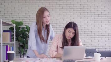 duas jovens mulheres asiáticas reunindo-se em um escritório em sua pequena empresa, sentadas lendo um relatório ou papel com sorrisos satisfeitos.