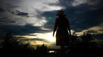 silhueta de mulher levantando as mãos com o sol poente ao fundo video