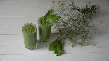 Smoothie verde misturado com ingredientes ou coquetel no fundo branco.