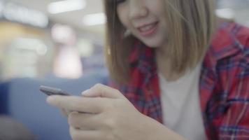 feliz mulher asiática usando e verificando seu smartphone enquanto está sentado na cadeira no corredor do terminal. video