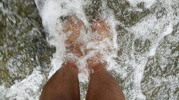 stretta di piedi rilassanti in una cascata.