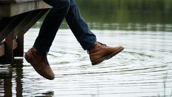 Hombre balanceando su pierna por el lago sentado en el borde de un muelle de madera