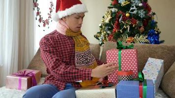 apuesto joven abriendo su regalo de navidad