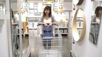 jovem mulher asiática anda de carrinho de compras, escolhendo móveis novos em armazém. video