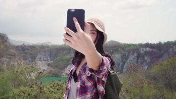 Asian backpacker woman taking a selfie on the top of a mountain. video