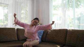mujer estirando en el sofá por la mañana