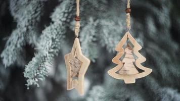 hölzerne Weihnachtsspielzeuge hängen an den Zweigen eines Weihnachtsbaumes