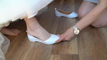 dama de honra ajuda noiva a calçar sapatos