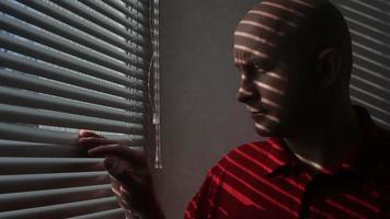 homem fica perto de janela em quarto de hotel video