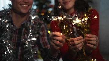 casal jovem feliz se divertindo com brilhos de fogo.