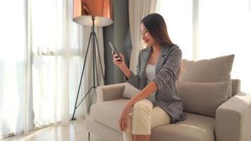 mujer mirando el teléfono sentado en un sofá
