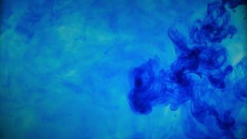 Blue color paint ink pouring over the glass with inky drops falling and abstract smoke explosion. video