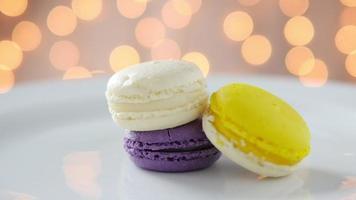 Macarons coloridos em chapa branca com fundo bokeh brilhante video
