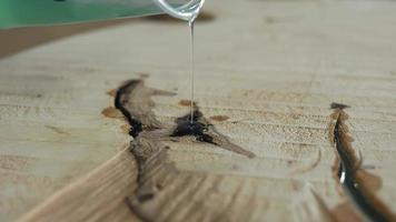 il boscaiolo riempie le crepe nel legno con resina epossidica