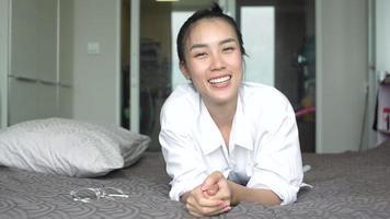 mujer acostada en la cama y sonriendo en casa.