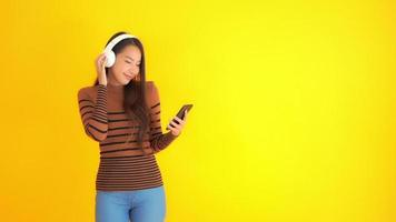 Woman listens to music with headphones on yellow background