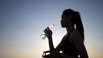 Woman drinking water at Sunset