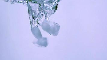 vertiendo cubitos de hielo en el agua
