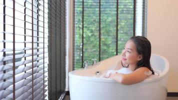 mulher asiática relaxando na banheira