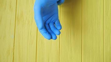 El médico se puso guantes quirúrgicos estériles azules en las manos
