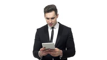 Shocked businessman reading bad news on a tablet