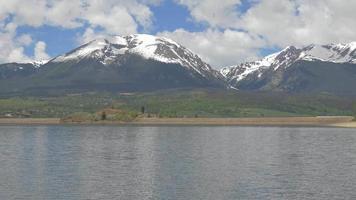 des voitures lointaines conduisent au bord du lac sous les montagnes rocheuses 4k
