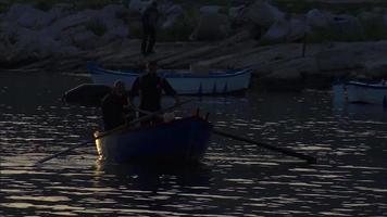 hombres en botes al atardecer