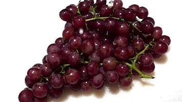 cámara lenta de gotas de agua sobre las uvas