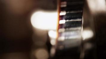 close-up extremo do projetor de filmes de 8 mm e um detalhe do filme com grandes rodas dentadas em um fundo claro em 4k