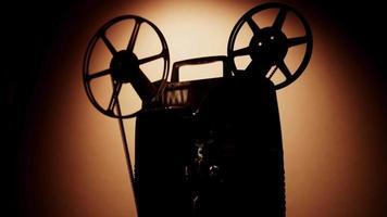 vista lateral de uma silhueta de pessoa ligando e desligando um projetor de filme de 8 mm com rolos de filme girando em 4k