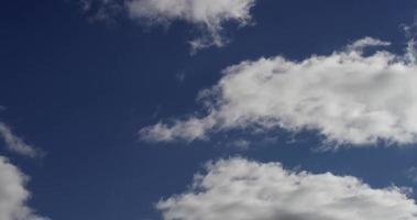 lapso de tempo de nuvens brancas de tamanhos diferentes se afastando e desaparecendo no céu azul em 4k video