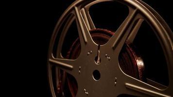 extrema close-up da bobina de filme girando mostrando reflexos de luz em fundo preto em 4k