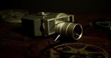panorâmica escura na mesa indo para a esquerda de duas bobinas, uma câmera e um filme caindo na superfície de madeira em 4k
