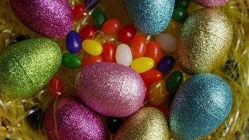 Foto giratoria de decoraciones de pascua y dulces en la colorida hierba de pascua - pascua 015