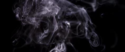 trama eterea di fumo bianco fluttuante e creando belle forme nell'oscurità in 4K