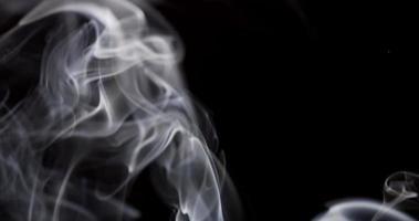 redemoinhos e espirais de fumaça branca preenchendo um fundo preto com belos padrões em 4k video