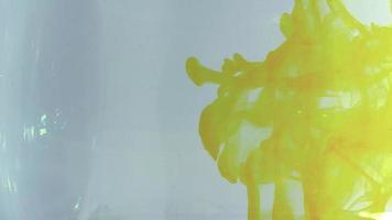 tinta amarilla creando una textura en el recipiente de agua