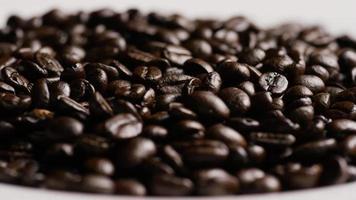 colpo rotante di deliziosi chicchi di caffè tostati su una superficie bianca - chicchi di caffè 076