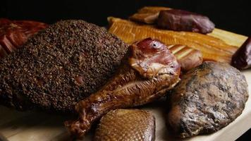 Rotating shot of a variety of delicious, premium smoked meats on a wooden cutting board - FOOD 053
