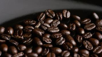 colpo rotante di deliziosi chicchi di caffè tostati su una superficie bianca - chicchi di caffè 015