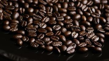 rotierender Schuss von köstlichen, gerösteten Kaffeebohnen auf einer weißen Oberfläche - Kaffeebohnen 014