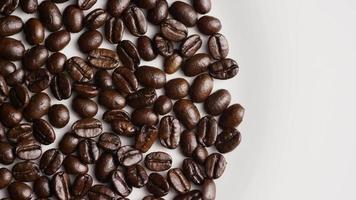 colpo rotante di deliziosi chicchi di caffè tostati su una superficie bianca - chicchi di caffè 029