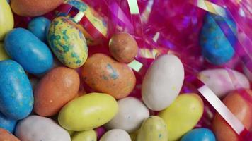Foto giratoria de coloridos dulces de pascua sobre un lecho de pasto de pascua - pascua 118