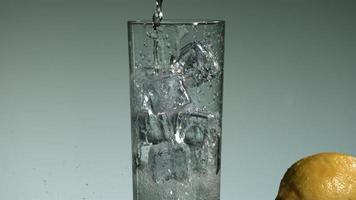 líquido transparente carbonatado que se vierte y salpica en cámara ultra lenta (1,500 fps) en un vaso lleno de hielo - líquido vertido 018