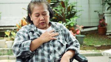 mulher idosa com doença cardíaca com as mãos no peito